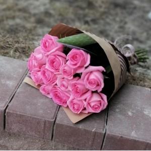 букет из 15 розовых роз в крафт бумаге